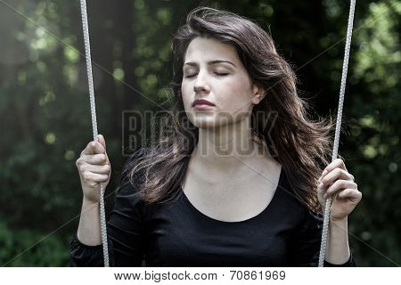 Woman Swinging With Closed Eyes