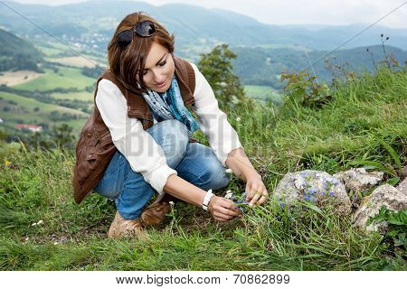 Young Woman Admires The Flowers At The Mountain Meadow