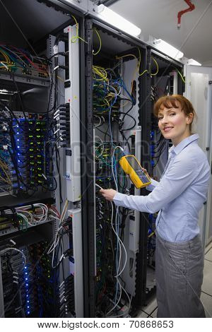 Technician using digital cable analyzer on server in large data center