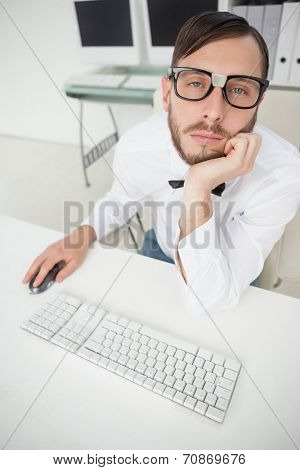 Nerdy bored businessman working on computer in his office