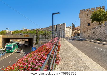 JERUSALEM, ISRAEL - JULY 10, 2014: Pedestrian walkway and urban road near Jaffa Gate - one of eight gates in the historic walls of the Old City of Jerusalem  built in 1583 by Suleiman the Magnificent.