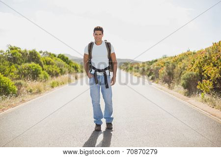 Full length portrait of a hiking man walking on countryside road