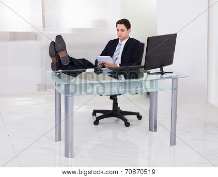 Relaxed Businessman Using Digital Tablet In Office