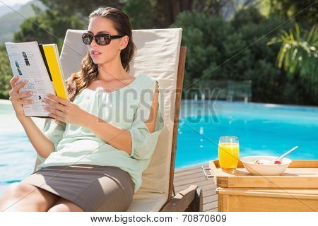 Beautiful young woman reading book by swimming pool with breakfast on table