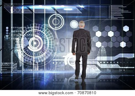 Businessman walking against hologram interface in office overlooking city