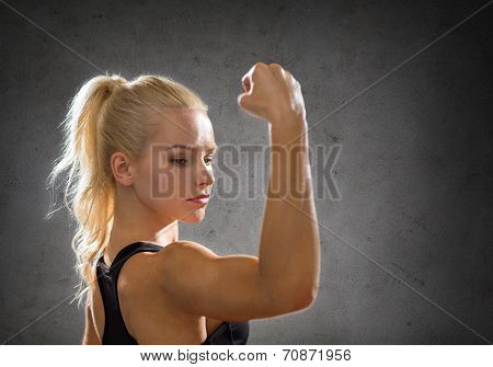 fitness, sport and strength concept - sporty woman flexing her biceps over concrete wall background