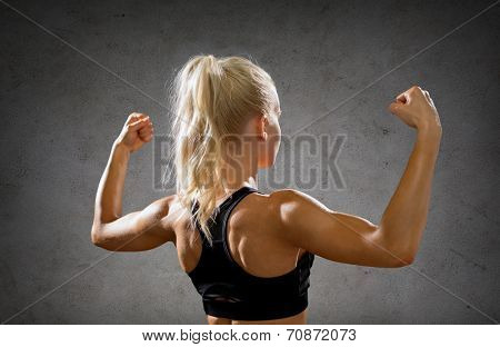 fitness, sport and strength concept - sporty woman form back flexing her biceps over concrete wall background