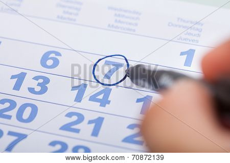 Businessman Marking Date On Calendar In Office