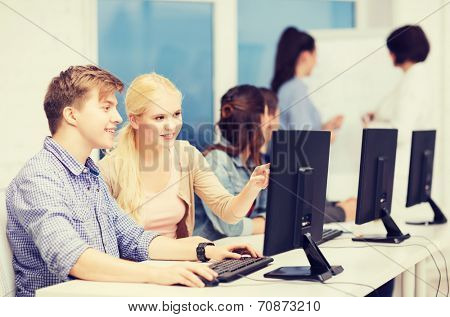 education, techology and internet concept - group of smiling students with computer monitor looking at teacher at school