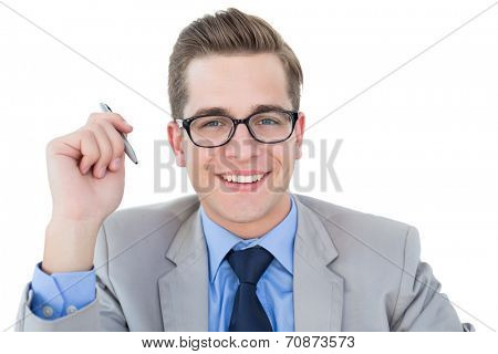 Nerdy businessman holding pen smiling at camera on white background
