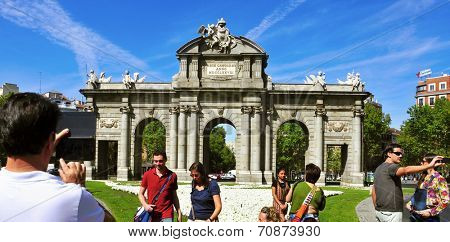 MADRID, SPAIN - AUGUST 13: Tourists taking pictures of La Puerta de Alcala on August 13, 2014  in Madrid, Spain. This historical gate is one of the most popular landmarks in the city