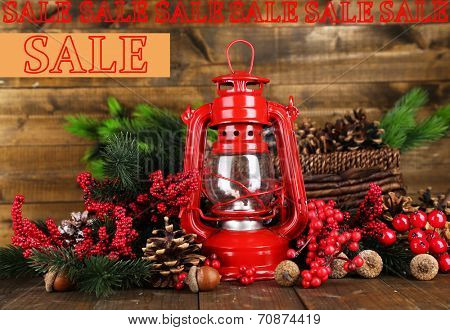 Concept of discount. Red kerosene lamp on wooden background