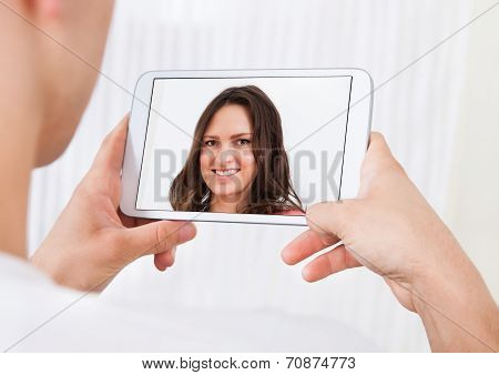Man Video Conferencing With Woman On Digital Tablet At Home