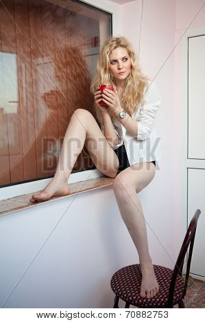 portrait of a young, blond woman, holding a mug with both her hands