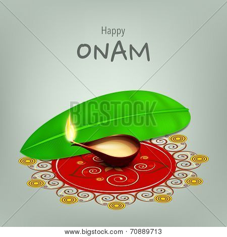 Illuminated oil lit lamp on beautiful rangoli with banana leaf on grey background for South Indian festival Onam celebrations.