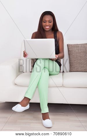 Young Woman Using Laptop While Sitting On Sofa In Living Room