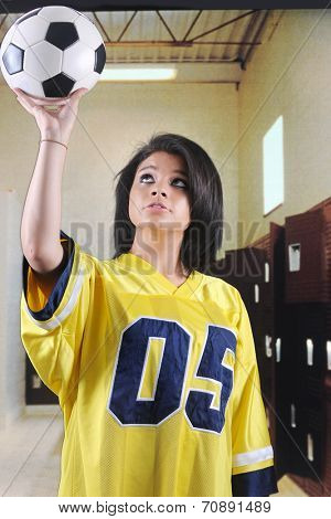 A beautiful teen girl in a locker room, catching a high soccer ball with one hand.