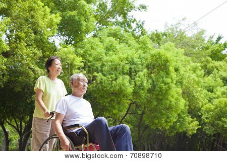 Asian Senior Man Sitting On A Wheelchair With His Wife