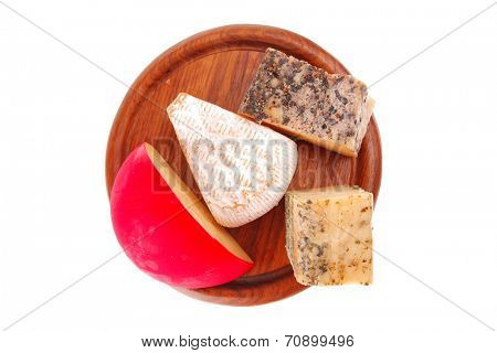 french cheeses on dark wooden plate on white