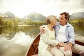 picture of life-boat  - Senior couple hugging on boat on mountain tarn - JPG