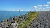 stock photo of dike  - Dike of rocks and basalt along a lake in summer - JPG