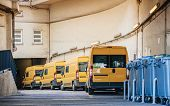 stock photo of trailer park  - Row of yellow delivery and service van trucks and cars in front of the entrance of a warehouse distribution logistic plant - JPG