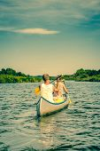 picture of canoe boat man  - Two men rowing down a river stream in a canoe - JPG