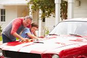stock photo of 11 year old  - Grandfather And Grandson Cleaning Restored Classic Car - JPG