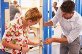 image of carpentry  - Teacher With Student In Carpentry Class Fitting Door Lock - JPG