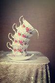picture of tilt  - Stack of tilted vintage teacups with milk spilling out  - JPG