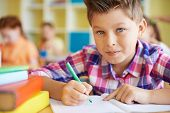 picture of pre-adolescents  - Calm schoolboy looking at camera while drawing at lesson - JPG