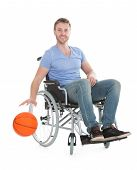 picture of paralympics  - Full length portrait of disabled player holding basketball on wheelchair over white background - JPG