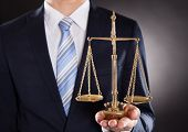 image of scales justice  - Midsection of businessman holding justice scale against black background - JPG