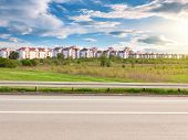 stock photo of tree lined street  - Side view of road and cityscape in background on sunny day - JPG