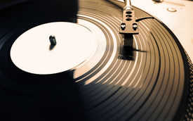 stock photo of outdated  - Old fashioned turntable playing a track from black vinyl in golden light - JPG