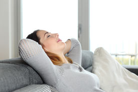 image of headings  - Happy relaxed woman resting on a couch at home with arms in the head - JPG