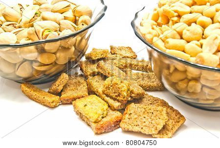 Two Plates With Roasted Nuts And Crackers
