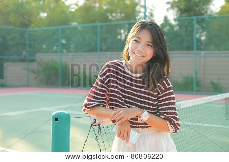 Portrait Of Beautiful Young Asian Woman Wearing White Clothes Skirt In Tennis Course With Happy Face
