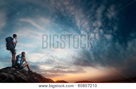 Two hikers relaxing on top of the rock and enjoying sunset