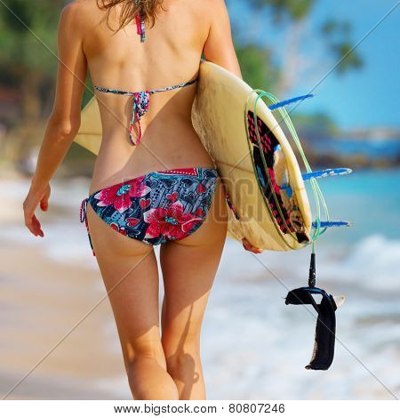 Close up shot of the young lady walking with surf board on sandy tropical beach