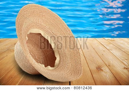 Summer hat on pool background