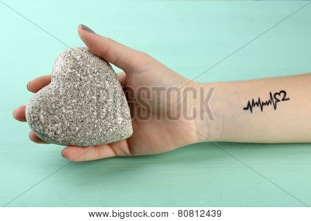 Female arm with tattoo holding decorative heart on wooden background