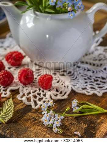 Still life with raspberries and green leafs