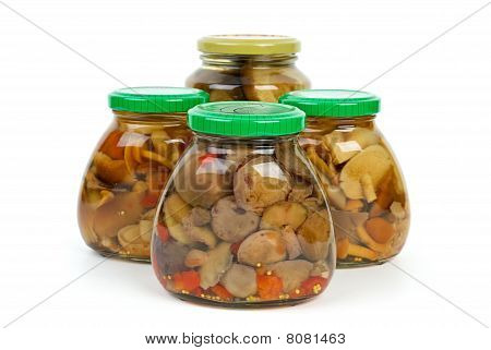 Four Glass Jars With Marinated Mushrooms