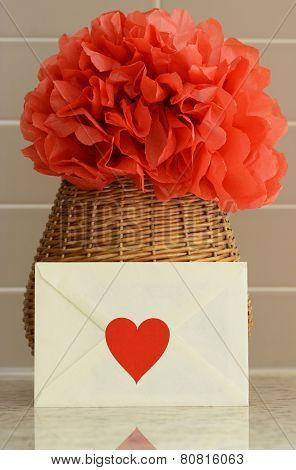 Vase basket with pom pom red tissue paper flower and a love letter