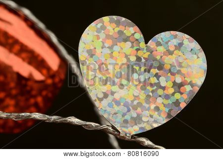 Single flat shiny white foil heart on silver string close up