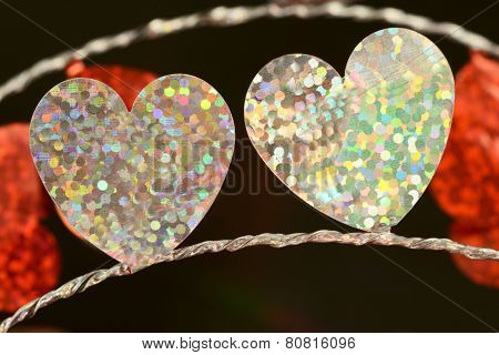 Two flat shiny white foil hearts on silver string close up