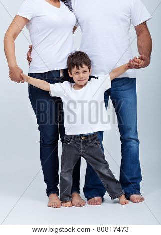 Happy little boy in the safe surroundings of his family - holding parents hands