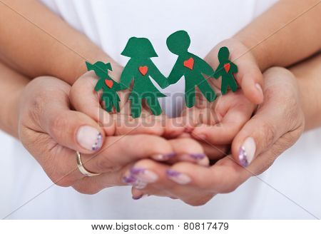 Loving family concept with adult and child hands holding paper people- shallow depth of field