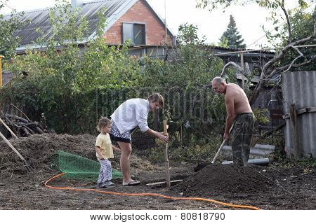 Family Planting Seedling In Garden
